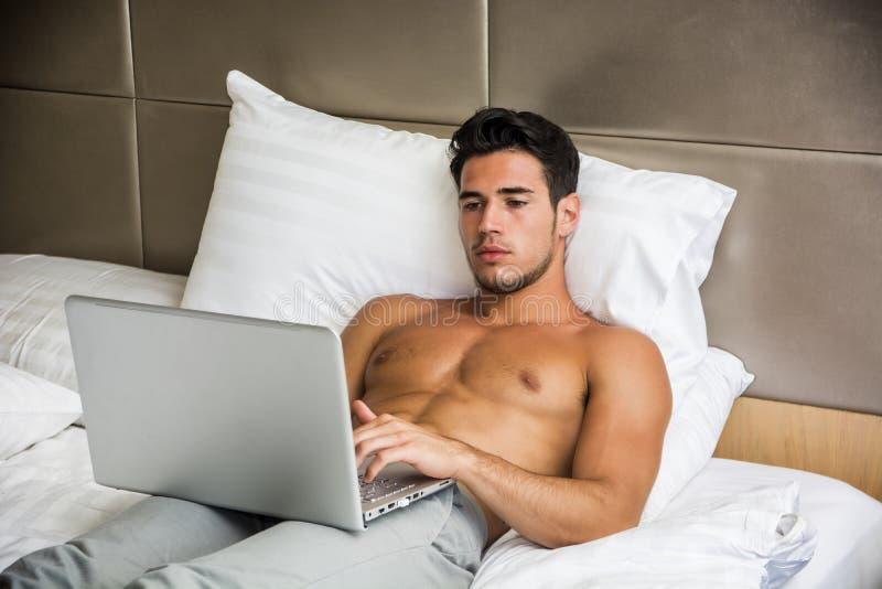 Jeune homme travaillant sur l'ordinateur portable dans la chambre à coucher photo stock