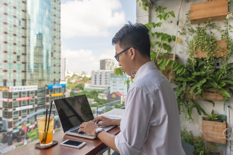 Jeune homme travaillant sur l'ordinateur portable extérieur le local commercial images stock