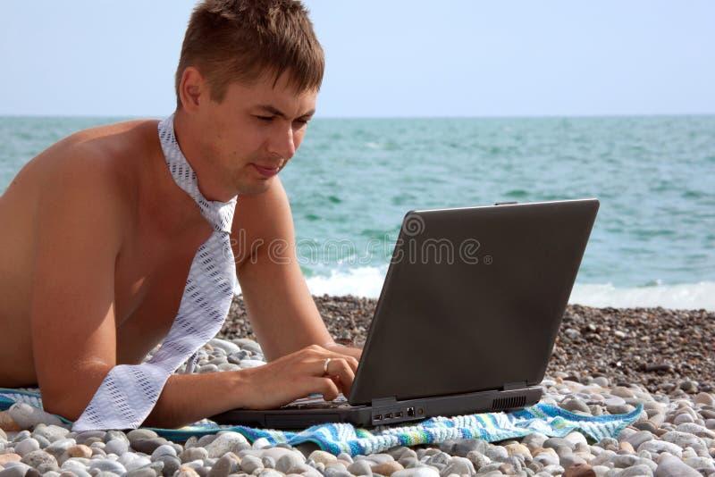 Jeune homme travaillant sur son ordinateur portatif sur la plage image stock