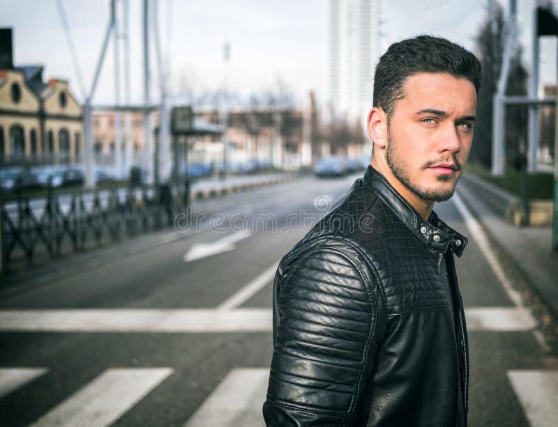 Jeune homme traversant une rue de ville, regardant la caméra photographie stock libre de droits