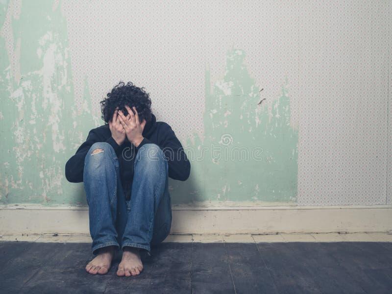 Jeune homme triste dans la chambre vide image stock