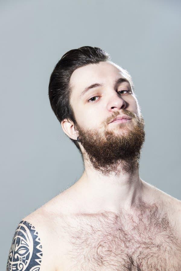 Jeune homme unshaved velu encré sexy musculaire brutal avec le tatouage sur son épaule et barbe photo stock