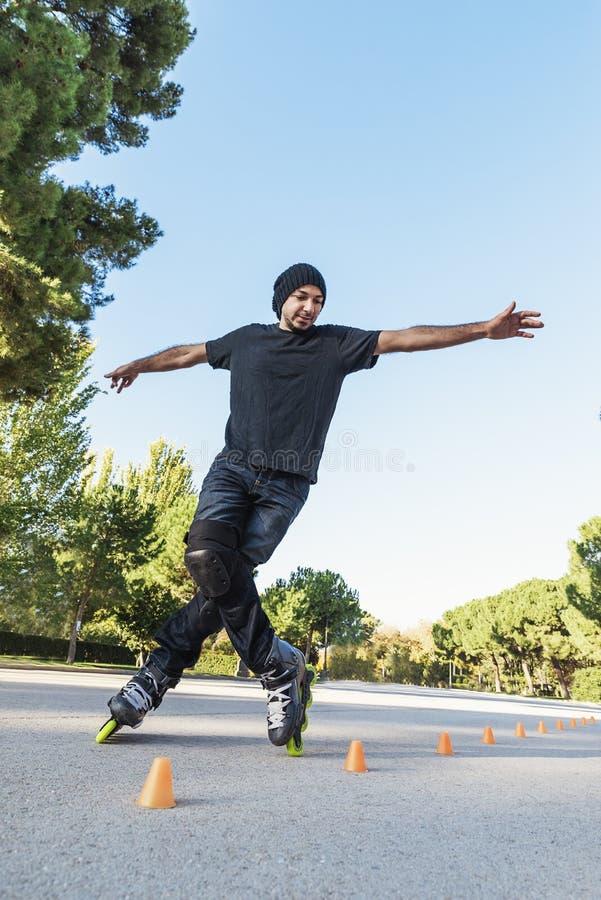 Jeune homme urbain sur des patins de rouleau sur la route à l'heure d'été photos libres de droits