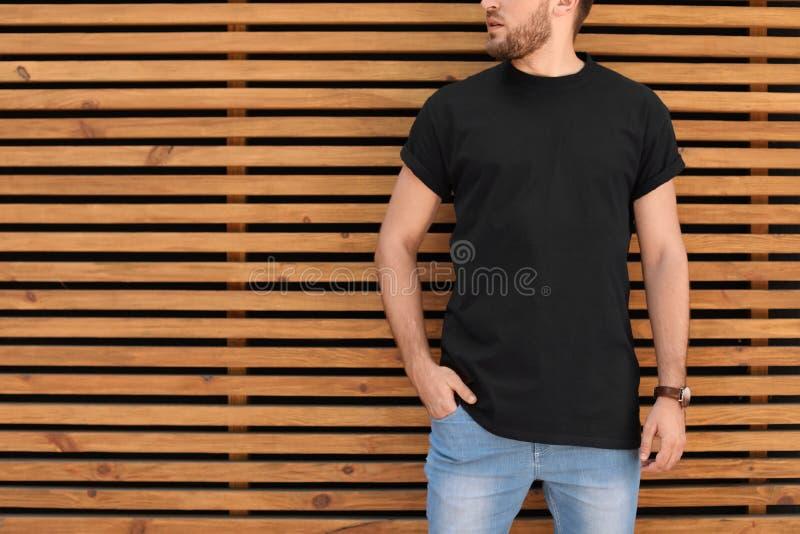 Jeune homme utilisant le T-shirt noir contre le mur en bois images libres de droits