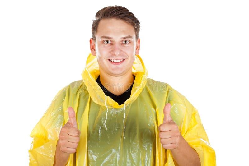 Jeune homme utilisant un imperméable jaune, montrant des pouces  image stock