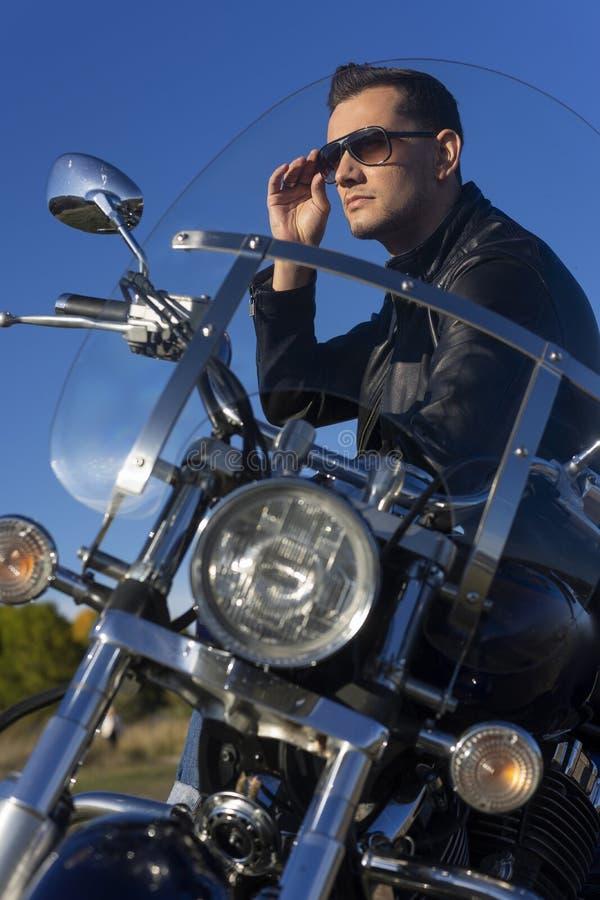 Jeune homme utilisant une veste en cuir noire, les lunettes de soleil et les jeans s images stock
