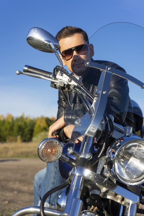 Jeune homme utilisant une veste en cuir noire, les lunettes de soleil et les jeans s photos stock