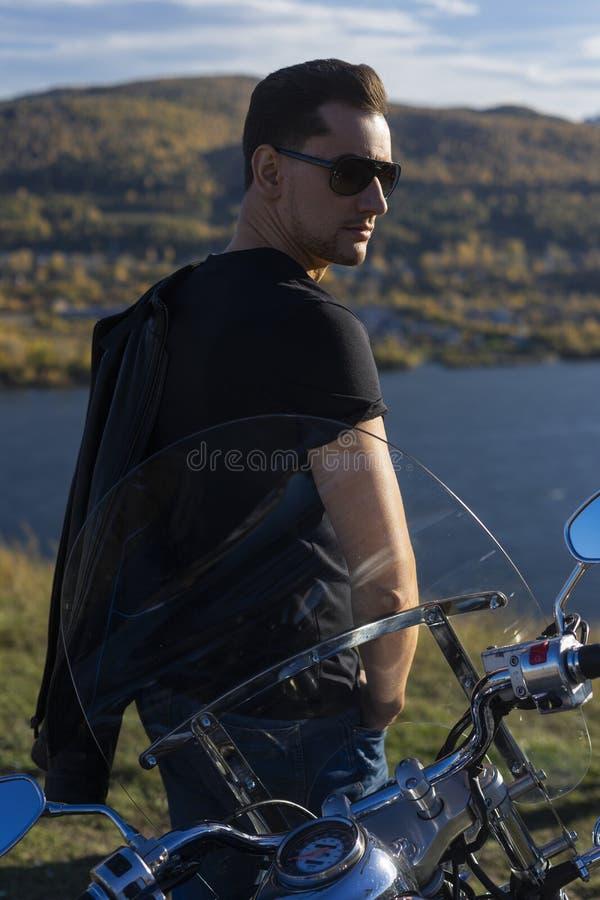 Jeune homme utilisant une veste en cuir noire, les lunettes de soleil et les jeans s image stock