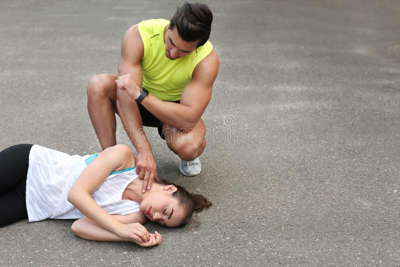 Jeune homme vérifiant l'impulsion d'inconscient sur la rue image stock