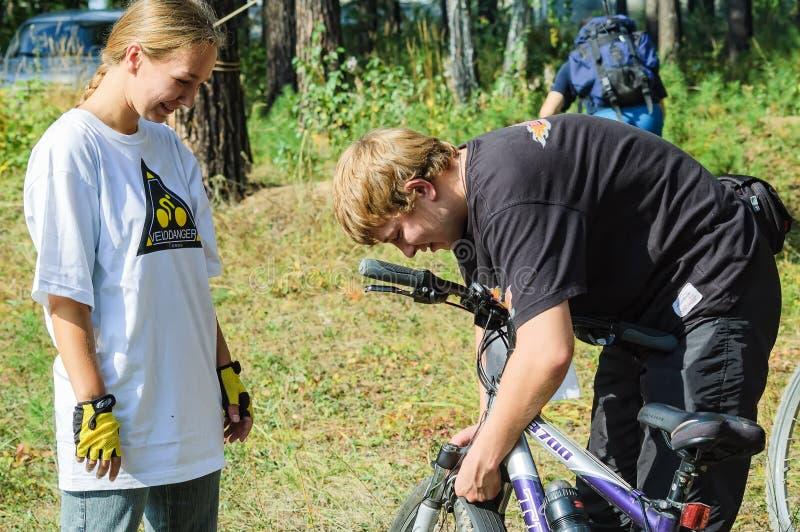Jeune homme vérifiant la bicyclette de la fille photos libres de droits