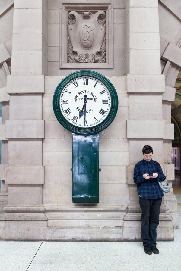 Jeune homme vérifiant son téléphone portable par le côté d'une grande horloge dans la gare ferroviaire centrale, Sydney, Australi image libre de droits
