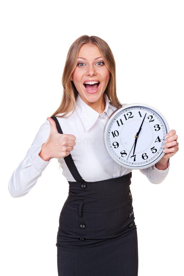 Jeune horloge joyeuse de fixation de femme d'affaires images stock