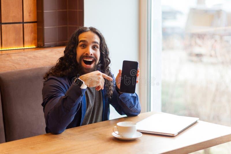 Jeune indépendant adulte beau étonnant positif d'homme dans le style occasionnel se reposant en café, dirigeant le doigt pour vid images libres de droits