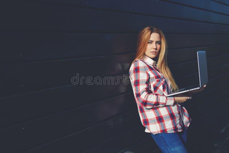 Jeune indépendant féminin employant le filet-livre pour le travail à distance pendant le temps gratuit images libres de droits