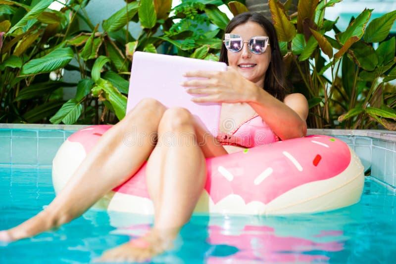 Jeune indépendant féminin s'asseyant avec un ordinateur portable en cercle gonflable dans la piscine Occupé pendant les vacances  photographie stock libre de droits