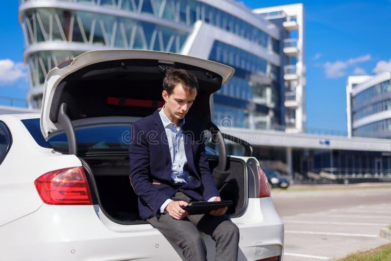 Jeune indépendant réussi d'homme d'affaires travaillant dehors dans la ville l'homme s'asseyent sur la botte de voiture avec le c image stock