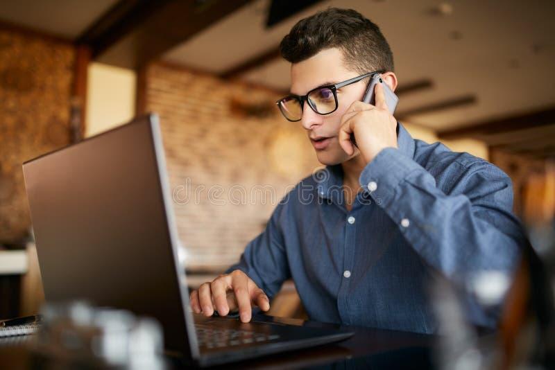 Jeune indépendant travaillant avec l'ordinateur portable et parlant sur le téléphone portable avec le client dans le bureau Homme image stock