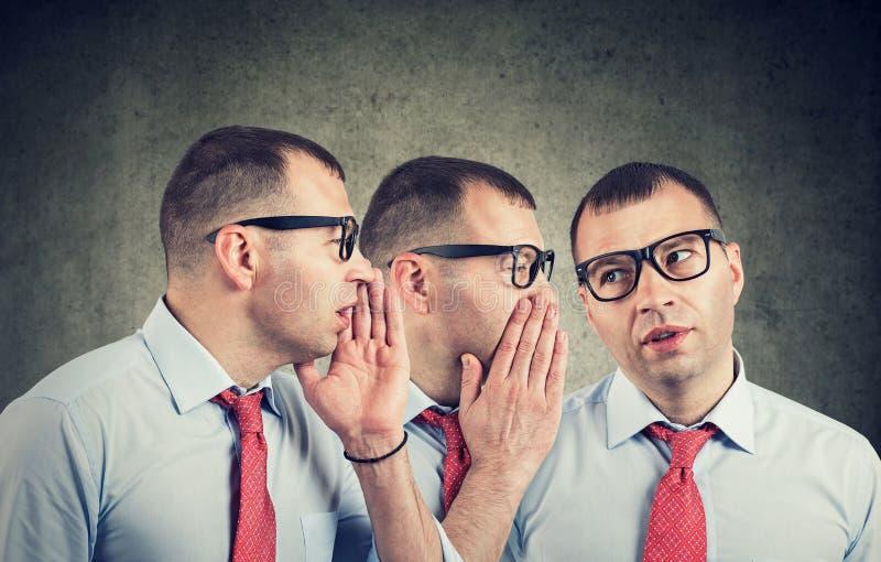 Jeune individu d'homme d'affaires chuchotant dans l'oreille photographie stock libre de droits