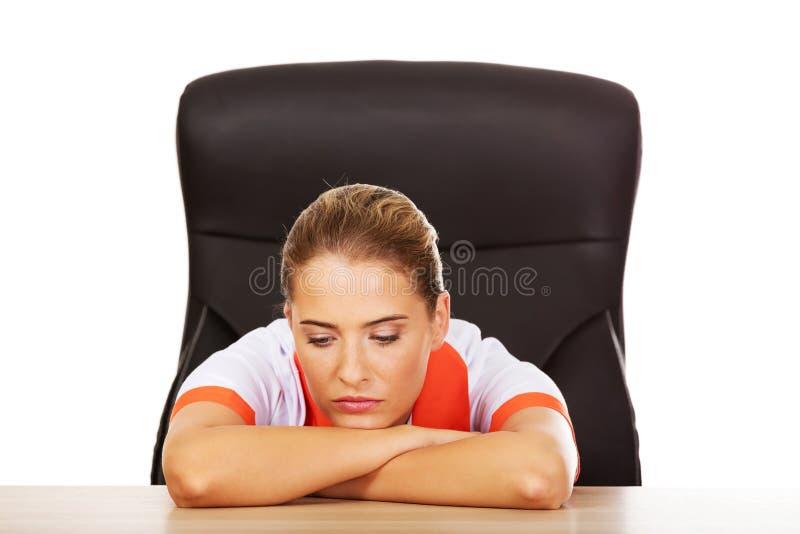 Jeune infirmière féminine fatiguée de doctoror s'asseyant derrière le bureau photo libre de droits