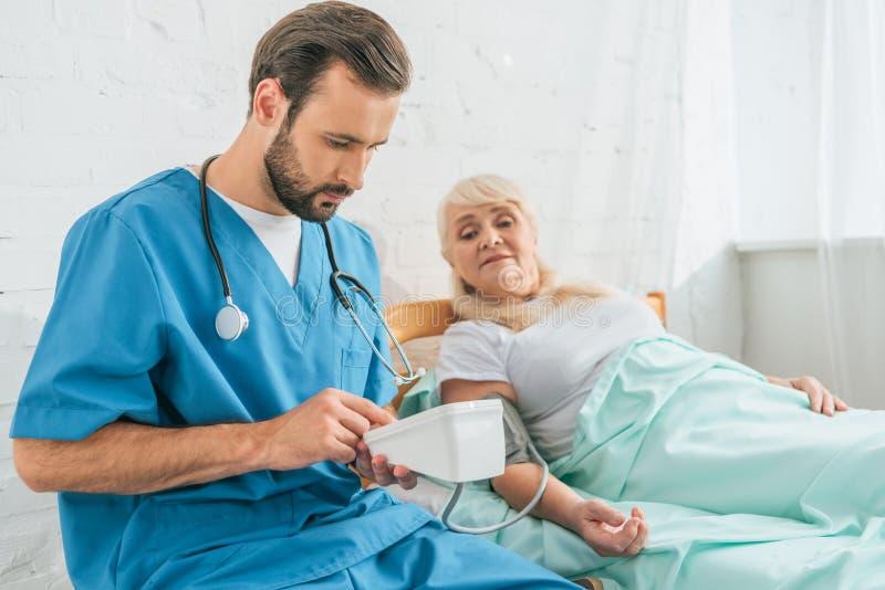 jeune infirmière masculine avec le stéthoscope tenant le moniteur de tension artérielle tout en mesurant la tension artérielle à  images libres de droits