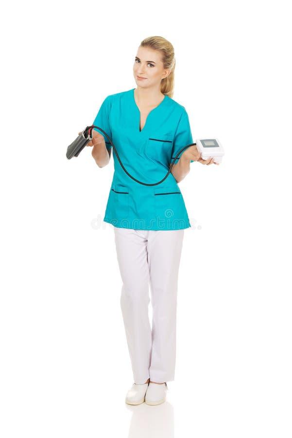 Jeune infirmière ou docteur similing avec l'indicateur de pression photos stock
