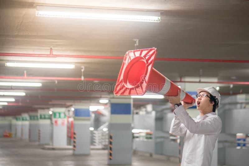 Jeune ingénieur asiatique hurlant cependant le cône de sécurité routière dans le parki photographie stock