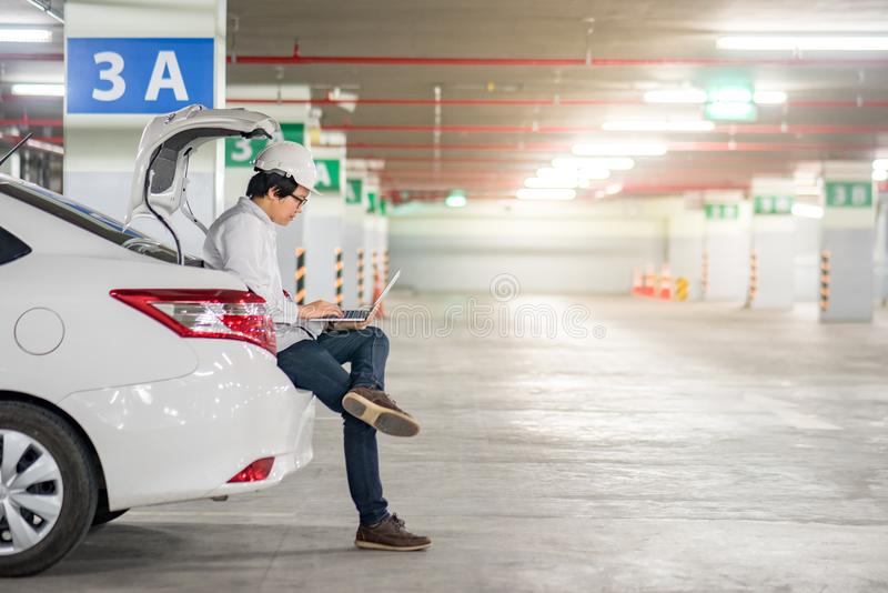 Jeune ingénieur asiatique travaillant avec l'ordinateur portable sur le tronc de voiture image libre de droits