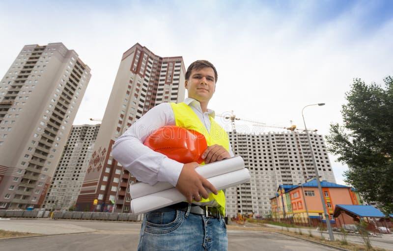 Jeune ingénieur de construction dans le gilet de sécurité tenant le masque photo stock