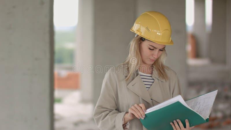 Jeune ingénieur de construction féminin d'architecte aux documents eximaining d'un chantier de construction photographie stock libre de droits