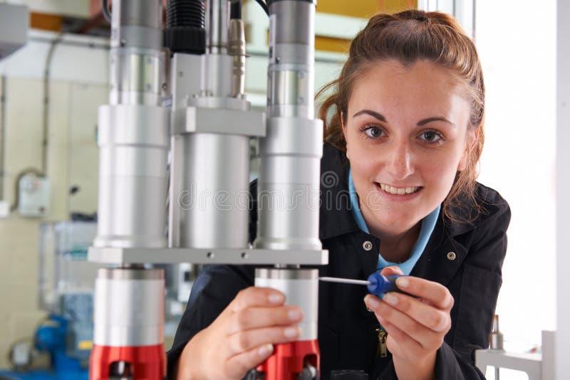 Jeune ingénieur féminin Working On Machine dans l'usine images libres de droits