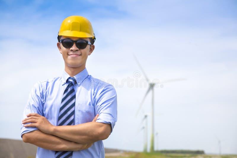 Jeune ingénieur sûr se tenant avec le générateur de vent image stock