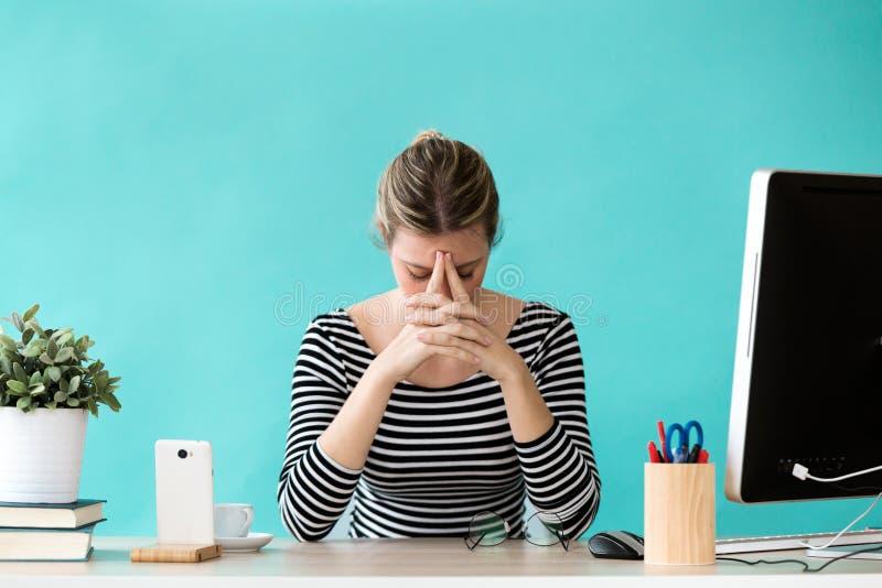 Jeune inquiétude de souffrance soumise à une contrainte de femme d'affaires tout en travaillant dans le bureau photographie stock