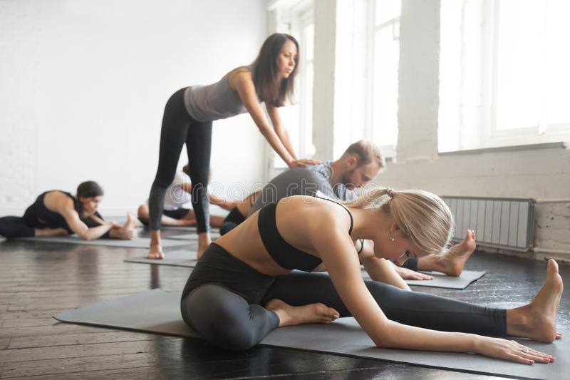 Jeune instructeur féminin de yoga enseignant la pose de Janu Sirsasana pour le GR images libres de droits