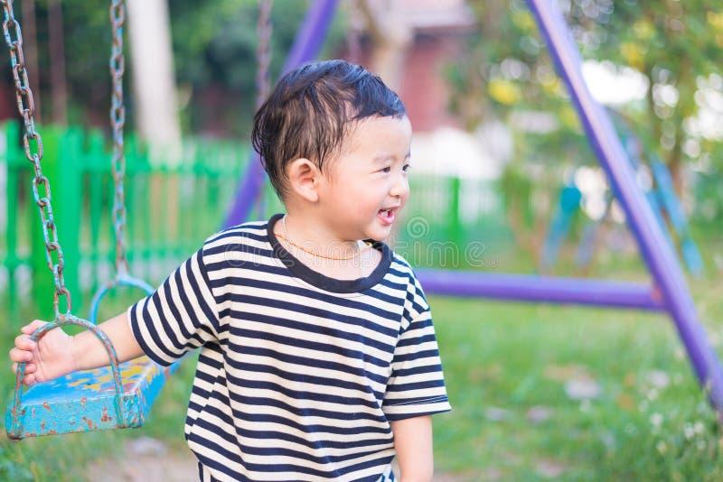 Jeune jeu asiatique de garçon un fer balançant au terrain de jeu sous photos stock