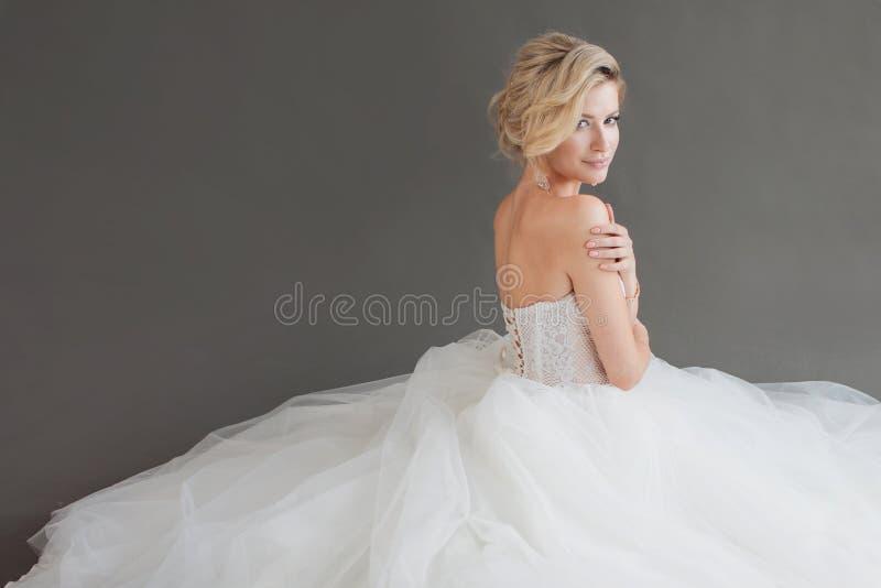 Jeune jeune mariée avec du charme dans la robe de mariage luxueuse Jolie fille dans le blanc Fond gris dos image libre de droits