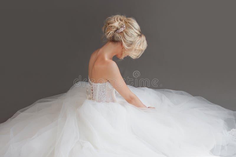 Jeune jeune mariée avec du charme dans la robe de mariage luxueuse Jolie fille dans le blanc Fond gris dos image stock