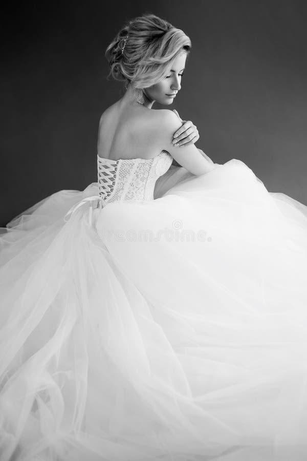 Jeune jeune mariée avec du charme dans la robe de mariage luxueuse Jolie fille dans le blanc Fond gris Photo arrière et blanche images stock