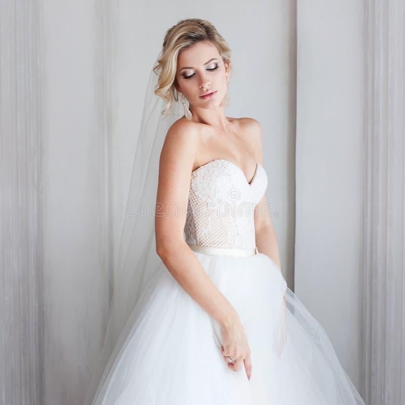 Jeune jeune mariée avec du charme dans la robe de mariage luxueuse Jolie fille, le studio de photo images stock