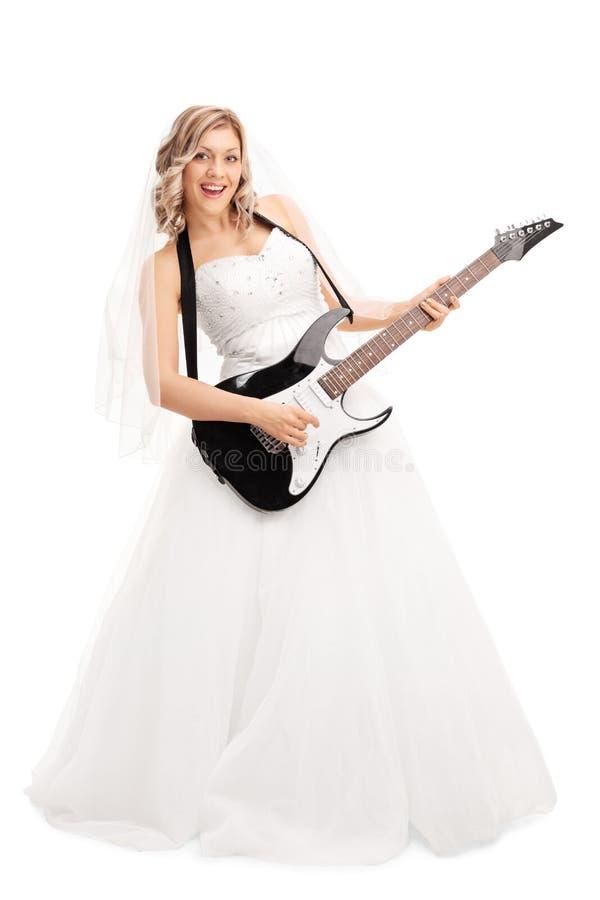 Jeune jeune mariée blonde jouant la guitare électrique photos libres de droits