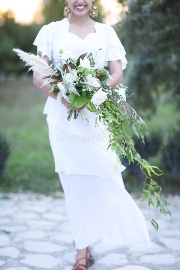 Jeune jeune mariée dans la robe de mariage blanche tenant le beau bouquet photographie stock