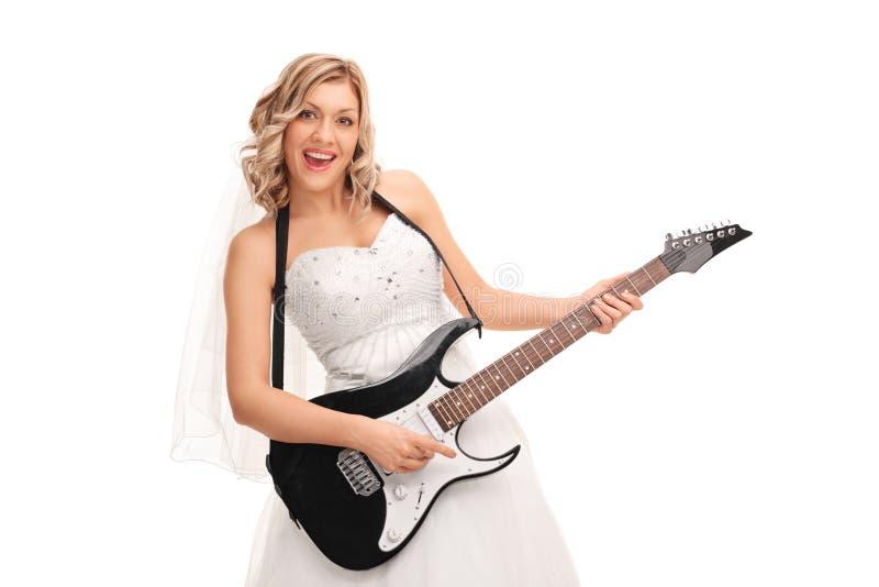 Jeune jeune mariée joyeuse jouant la guitare électrique photo stock