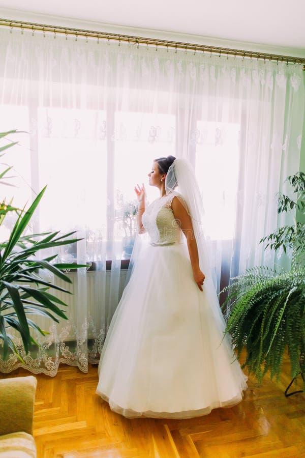 Jeune jeune mariée magnifique regardant la fenêtre dans sa chambre photographie stock libre de droits