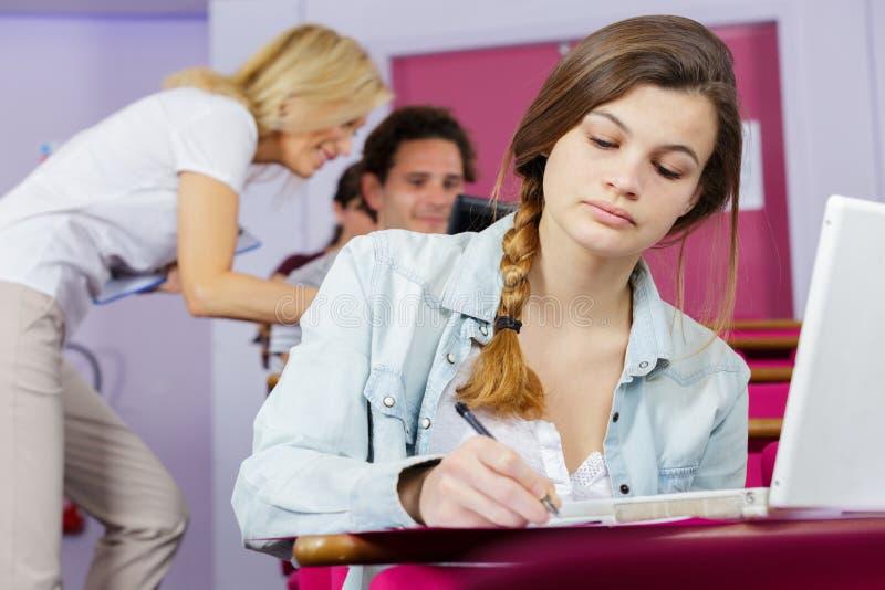 Jeune joli étudiant universitaire féminin à l'aide de l'ordinateur portable photo libre de droits