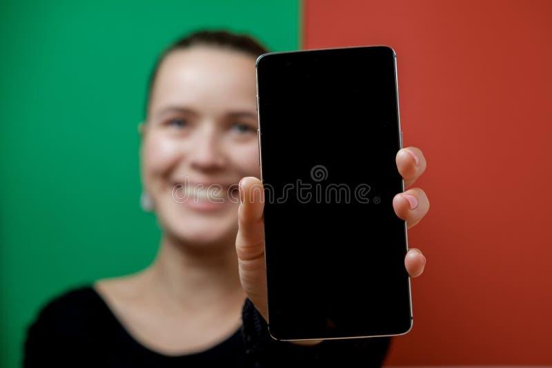 Jeune joli affichage d'apparence de femme de sa nouvelle cellule de mobile de contact photographie stock