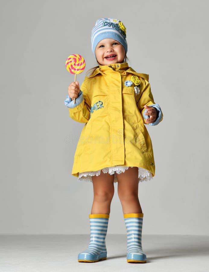 Jeune joli enfant de fille d'enfant en bas âge avec la grande sucrerie douce de lollypop dans la guêpe et des bottes en caoutchou photographie stock