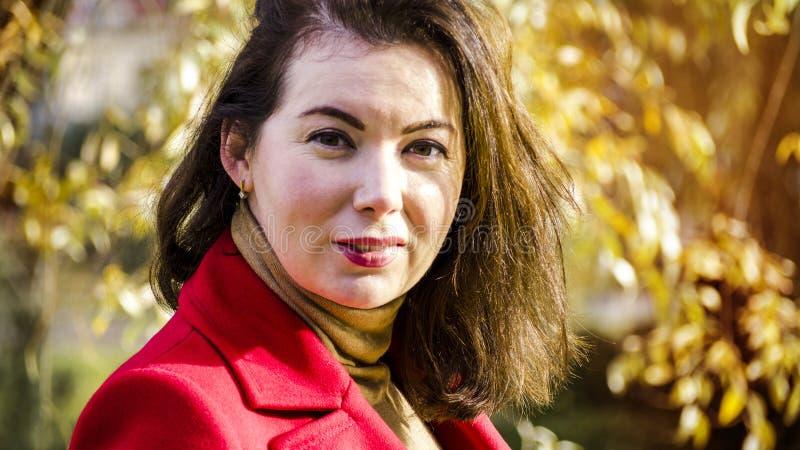 Jeune joli femme au stationnement d'automne image stock
