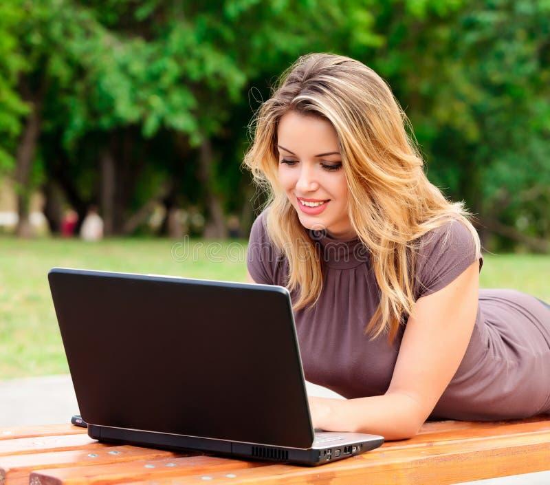 Jeune joli femme avec l'ordinateur portatif images libres de droits