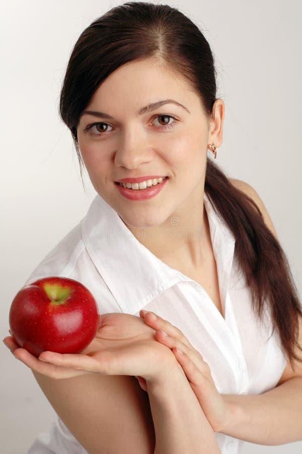 Jeune joli femme avec la pomme rouge photographie stock libre de droits