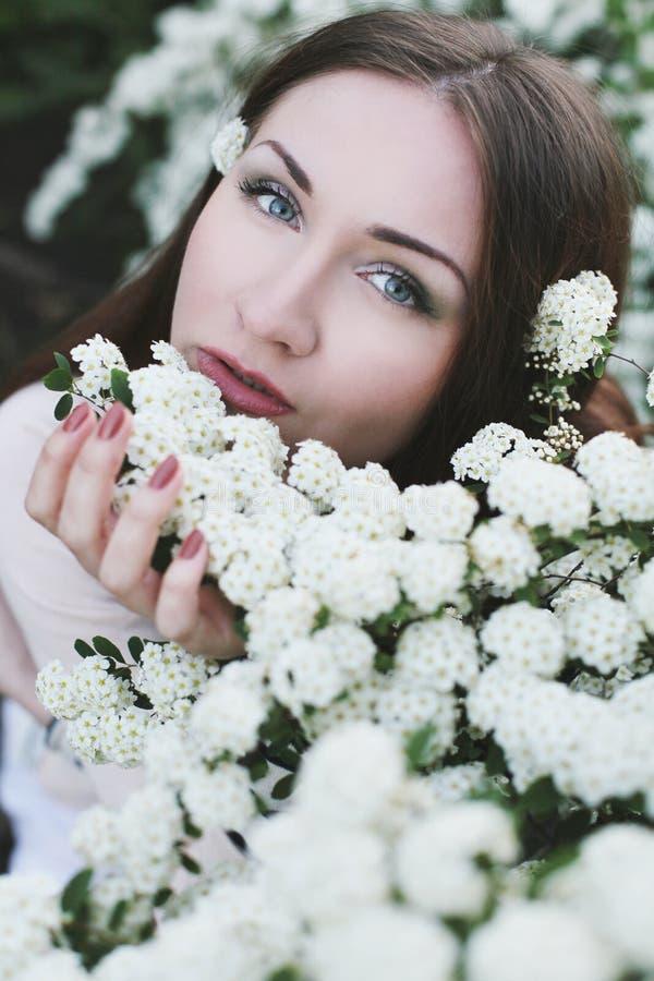 Jeune joli femme près de buisson de fleur photo stock