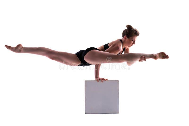 Jeune jolie brune faisant des exercices sur le cube photographie stock libre de droits
